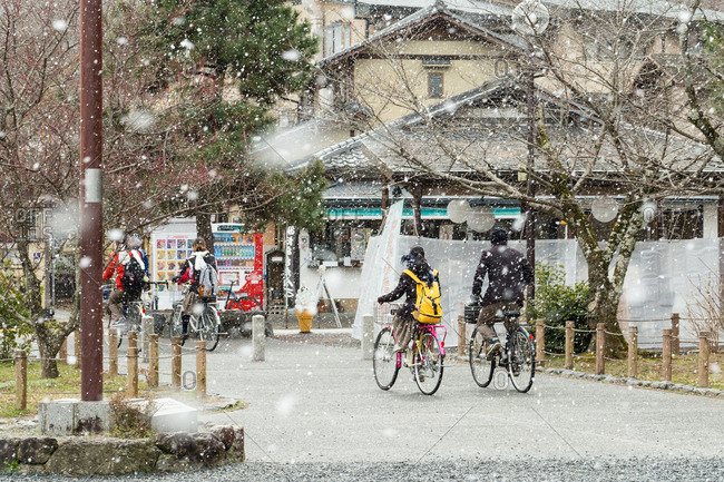 Kyoto, JAPAN - March 10, 2014: Students riding a bike in snowy street.