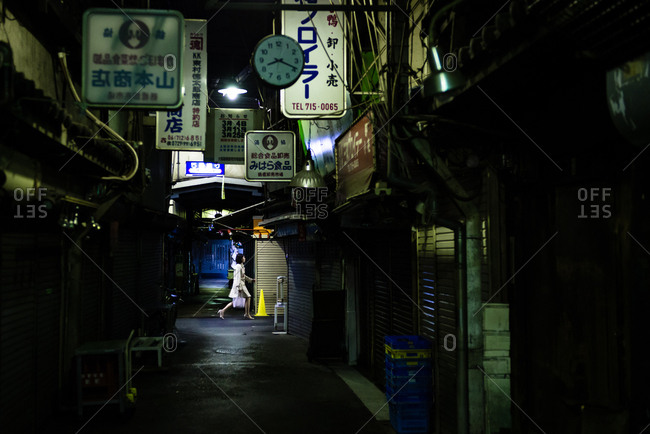 Osaka, JAPAN - March 20, 2015: Young woman walking on street at night.