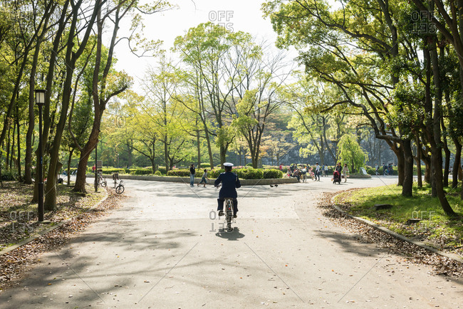 Osaka, JAPAN - April 18, 2015: Police officer riding bicycle in park.