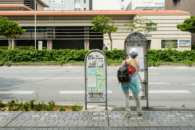 Naha, JAPAN - June 28, 2015: Old woman waiting for a bus.