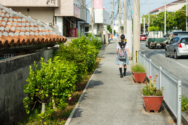 Okinawa, JAPAN - June 29, 2015: Schoolgirl in Okinawa street.