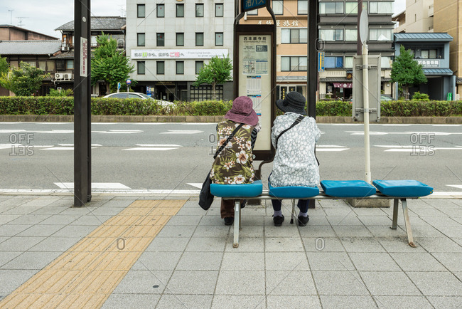 Kyoto, JAPAN - July 12, 2015: Elderly women waiting at bus stop, Kyoto.