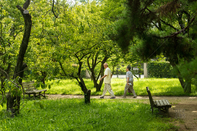 Kyoto, JAPAN - July 12, 2015: Elderly couple walking in the Kyoto gosho park.