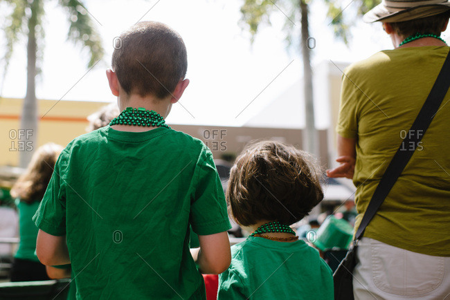 Children wearing green and watching a St. Patrick's Day parade.