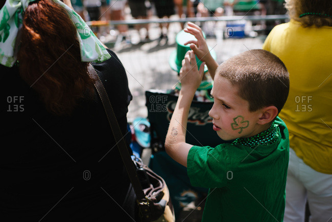 Boy trying to catch beads at a St. Patrick's Day parade