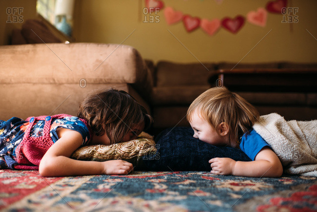 Sisters lying on pillows on the floor looking at each other