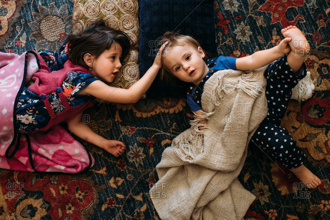 Sisters lying on pillows on a rug at home
