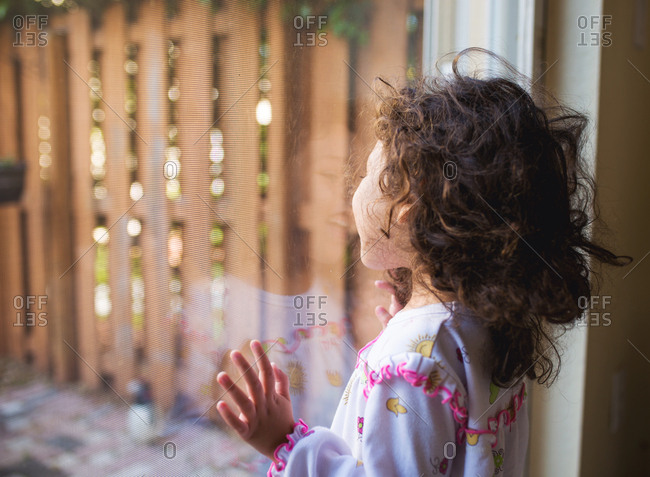 Toddler girl looking out sliding door