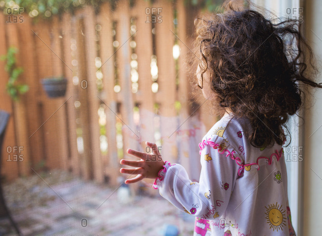 Toddler girl looks out sliding door