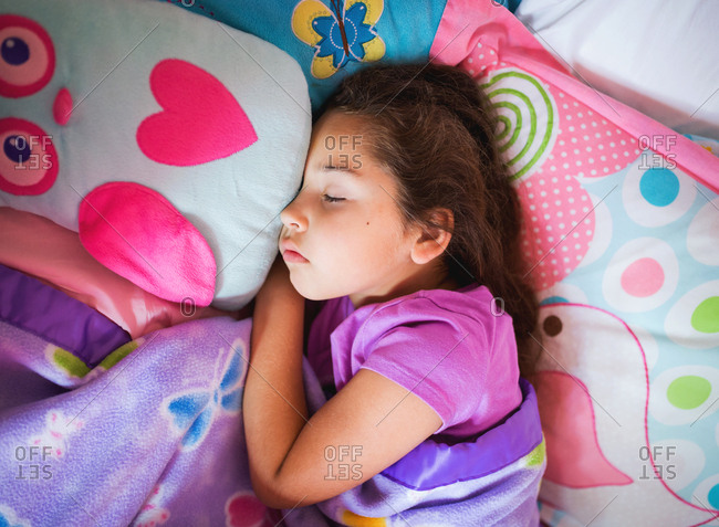 Young girl sleeping with owl pillow