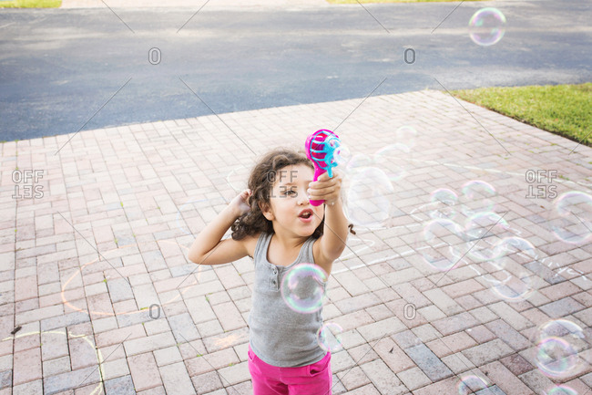Young girl playing with bubbles in driveway