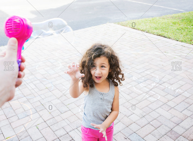 Young girl prepares for bubbles coming from bubble blower