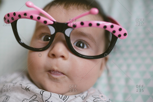Baby girl wearing butterfly glasses