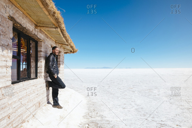 Man leaning on a salt hut looking to the  Uyuni Salt Flat (Salar de Uyuni) in the Altiplano, Bolivia