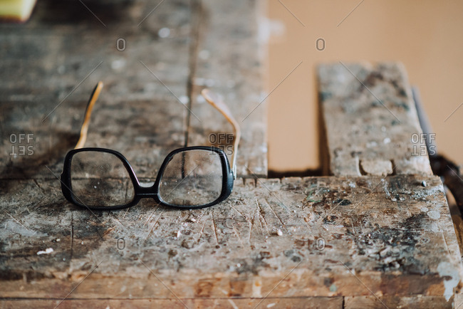 Eyeglasses on a dirty workbench