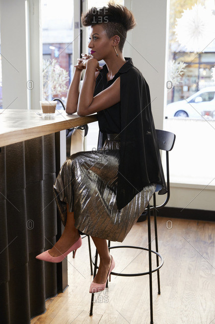 Trendy young woman wearing silver skirt in a cafe