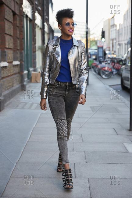 Woman wearing silver jacket and sunglasses walking in street