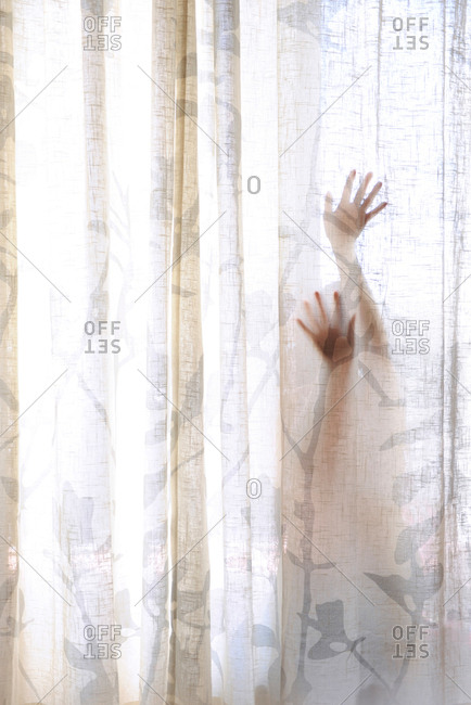 Woman's hands hiding behind a curtain