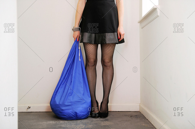 Sexy woman wearing fishnet stockings and holding a bag of laundry