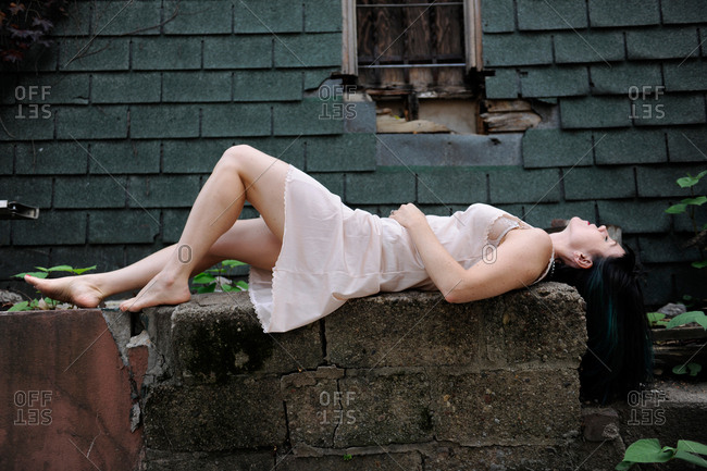 Woman wearing a slip laying on a decaying wall