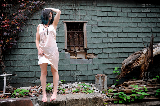 Woman wearing a slip standing amidst a decaying building