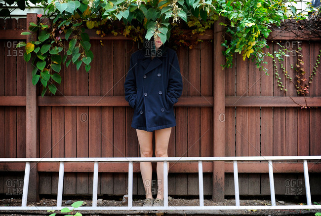 Girl wearing nothing but a coat hiding behind leaves