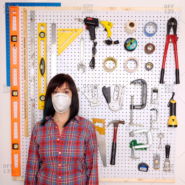 Woman wearing a mask standing in front of a wall of tools