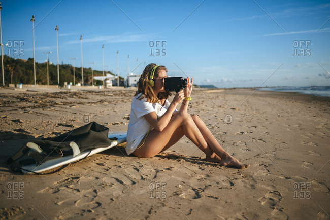 Young woman recording with old video camera on the beach