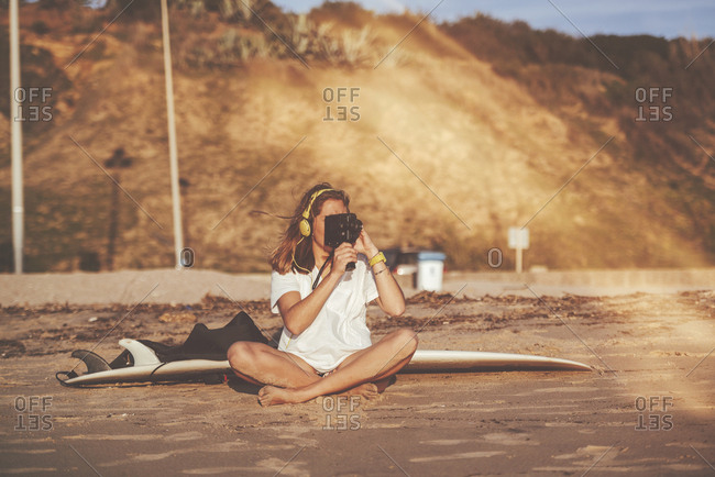 Woman recording with an old video camera on beach