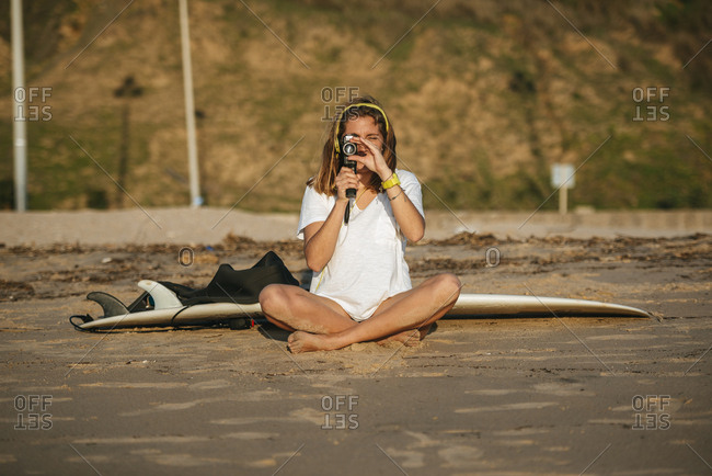 Woman recording with a vintage video camera on beach