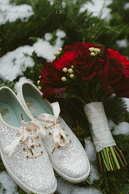 Sparkly canvas shoes by red flowers
