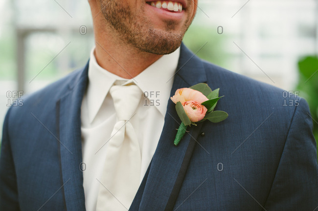 Groom wearing pink rose boutonniere