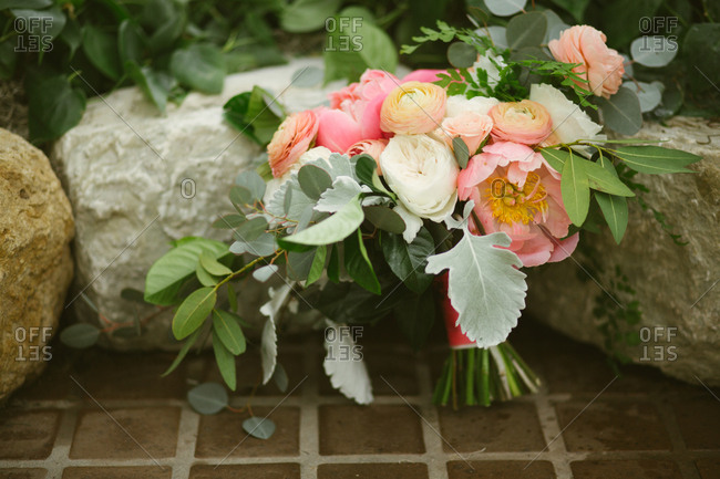 Peony wedding bouquet against stones