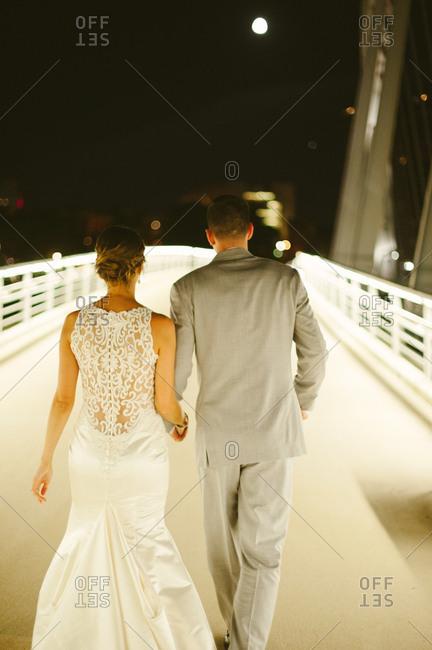 Bride and groom on footbridge at night