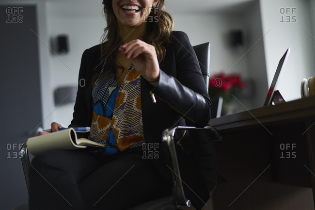 Midsection of happy businesswoman sitting with note pad on chair in office