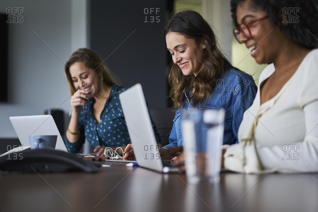Happy businesswomen using laptops and digital tablet at conference table in creative office