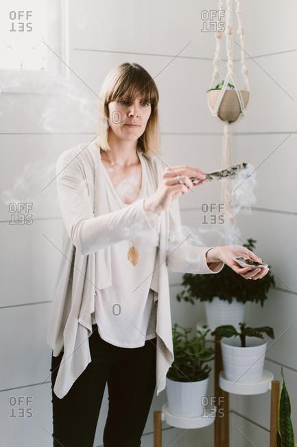 Woman burning sage indoors