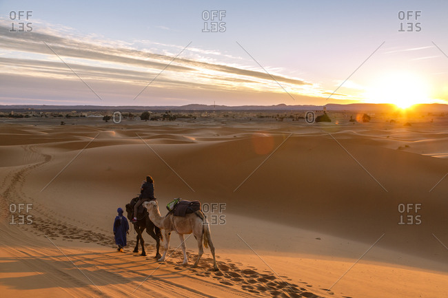 Merzouga, Morocco - November 24, 2016: Tuareg man with camels and tourists at the Erg Chebbi sand dunes, Sahara Desert