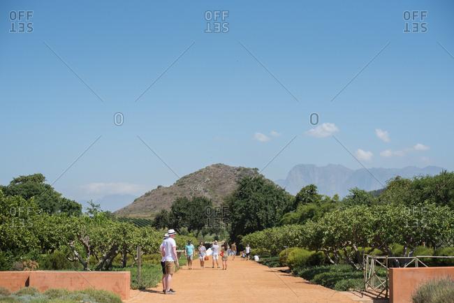 Stellenbosch, South Africa - July 22, 2015: Tourists on a garden path on a wine estate
