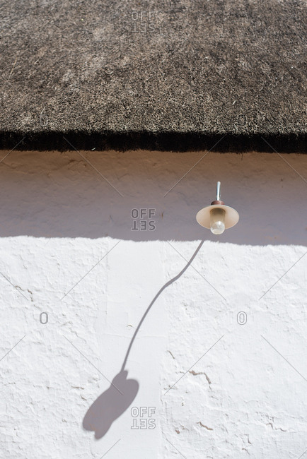 Light with shadow on a white building