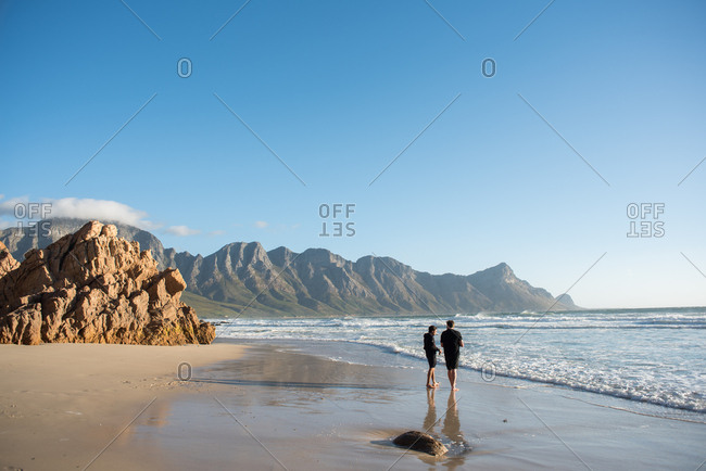 Cape Town, South Africa - July 22, 2015: Two men walking on the beach on the coast of Cape Town, South Africa