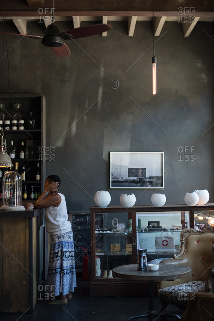 Cape Town, South Africa - January 9, 2017: Woman standing at a bar counter