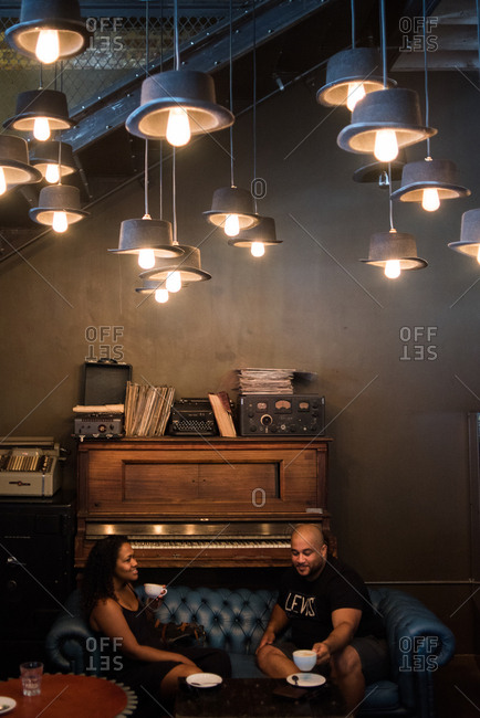 Cape Town, South Africa - January 9, 2017: Couple lounging on sofa in a caf� with top hat lights