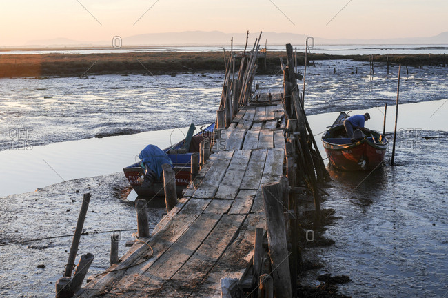Carrasqueira, Comporta, Portugal - July 22, 2015: Fisherman in his boat beside wooden jetty