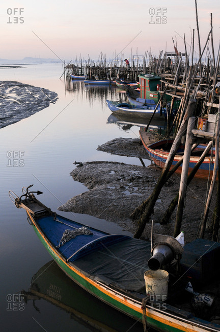 Carrasqueira, Comporta, Portugal - July 22, 2015: Wooden stilt docks and boats at sunset