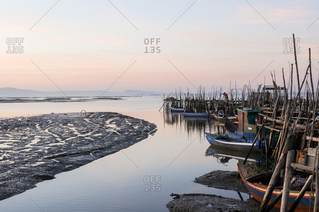 Carrasqueira, Comporta, Portugal - July 22, 2015: Wooden stilt docks and boats in the harbor at sunset