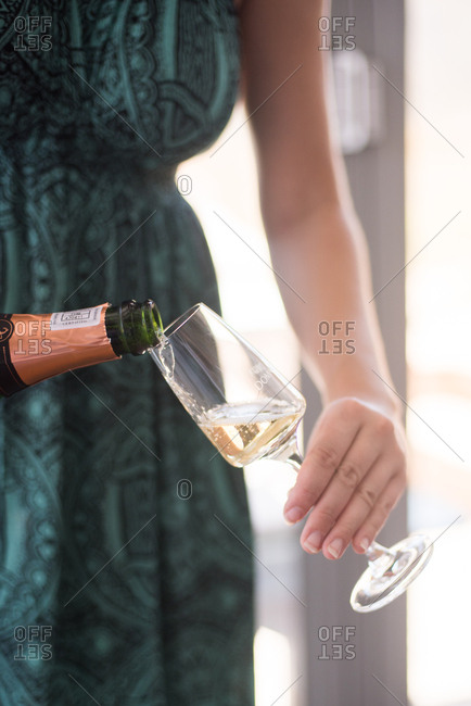 Hermanus, Western Cape, South Africa - July 22, 2015: Woman pouring glass of champagne