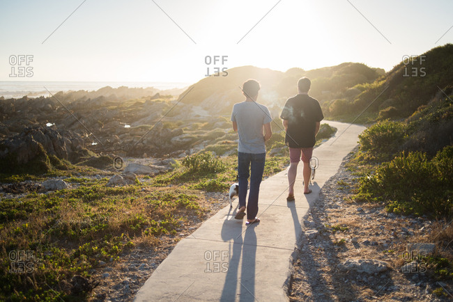 Two men walking dogs at sunrise in Hermanus in Western Cape, South Africa