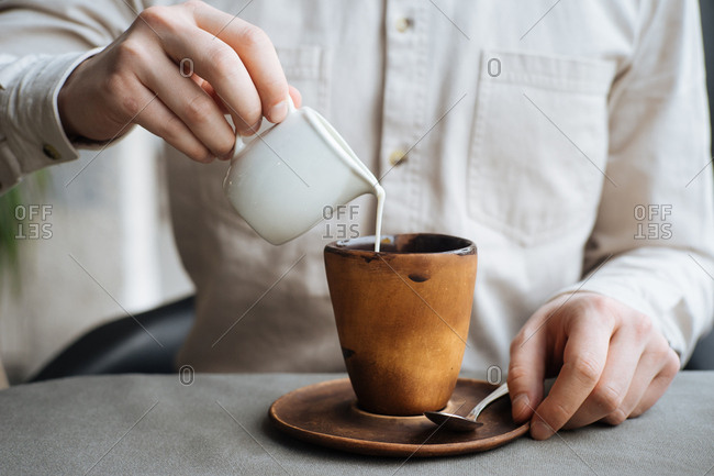 Man pouring milk into his coffee