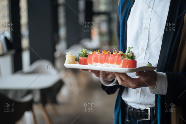 Server carrying dish with tuna rolls in a restaurant